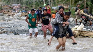 Residents cross a river at the flash flood-hit village of Andap, New Bataan township, Compostela Valley in southern Philippines, Wednesday, Dec. 5, 2012. (AP / Bullit Marquez)