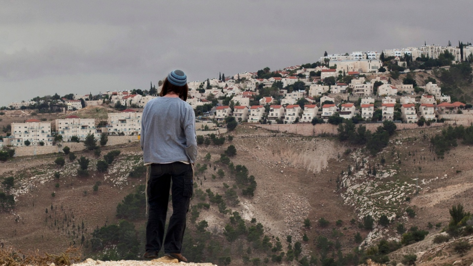 A Jewish settler looks at the West bank settlement of Maaleh Adumim, from the E-1 area on the eastern outskirts of Jerusalem, Wednesday, Dec. 5, 2012. (AP / Sebastian Scheiner)
