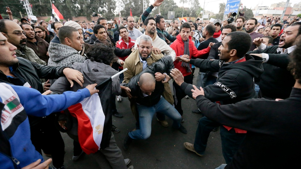 Egyptian President Mohammed Morsi's supporters beat an opponent, center, during clashes outside the presidential palace, in Cairo, Egypt, Wednesday, Dec. 5, 2012. (AP / Hassan Ammar)