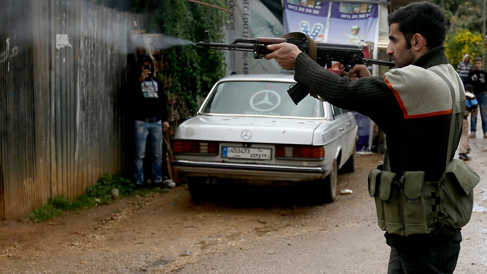 A Sunni gunman fires his weapon during clashes that erupted between pro and anti-Syrian regime gunmen in the northern port city of Tripoli, Lebanon, Wednesday, Dec. 5, 2012. (AP / Hussein Malla)
