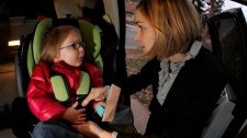 In this Dec. 18, 2009 photo, Anne Epperson unbuckles her daughter Madeline, age 3, from her car seat at their home. (AP / Charlie Riedel)