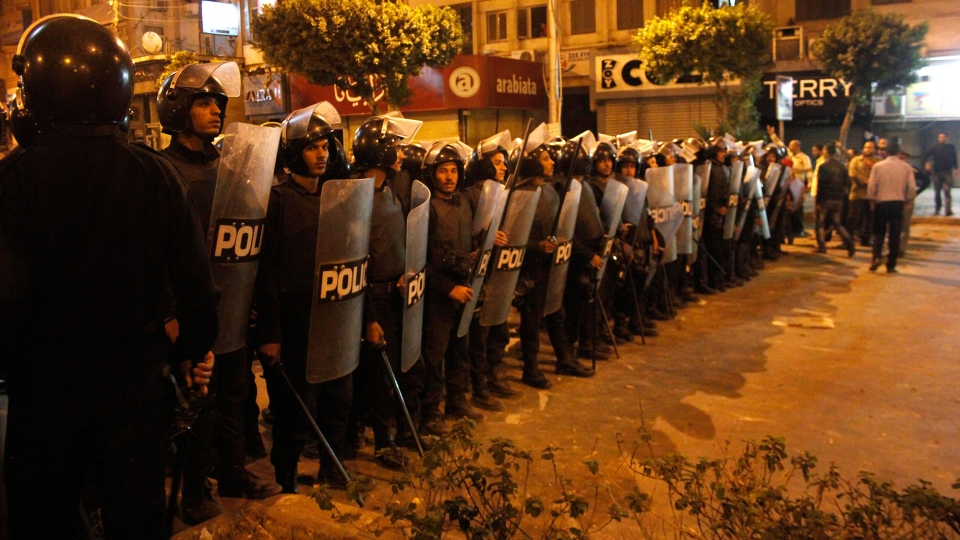 Egyptian riot police stand guard during clashes between supporters and opponents of Egyptian President Mohammed Morsi outside the presidential palace in Cairo, Egypt on Wednesday, Dec. 5, 2012. (AP / Mostafa Elshemy)