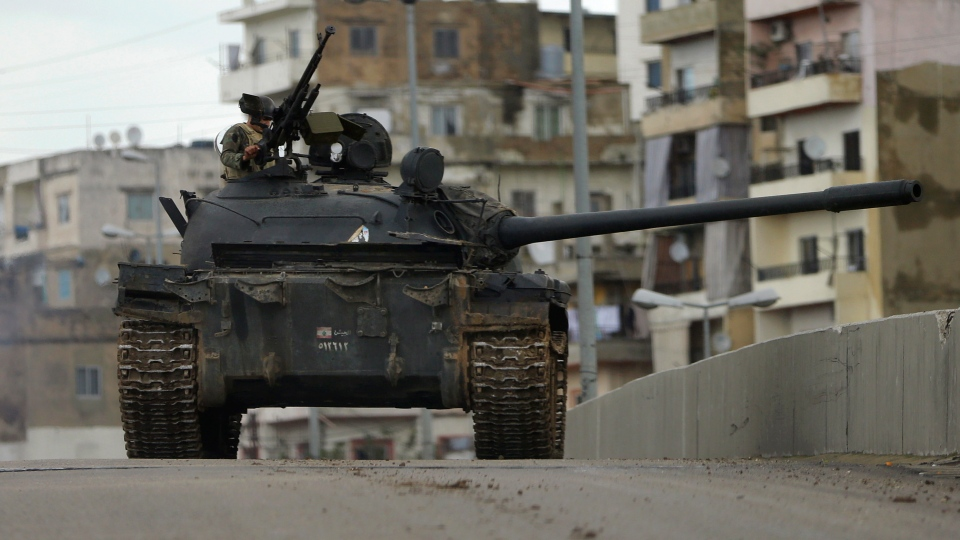 A Lebanese army soldier, stands on top of a tank during clashes that erupted between pro and anti-Syrian regime gunmen in the northern port city of Tripoli, Lebanon on Wednesday, Dec. 5, 2012. (AP / Hussein Malla)