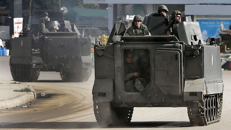 Lebanese army soldiers patrol in armored vehicles after clashes erupted between pro and anti-Syrian regime gunmen in the northern port city of Tripoli, Lebanon, Wednesday, Dec. 5, 2012. (AP / Hussein Malla)