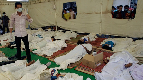 A Cambodian medic checks the bodies of stampede victims laid at Preah Kossamak Hospital in Phnom Penh, Cambodia, Tuesday, Nov. 23, 2010. (AP / Sakchai Lalit)
