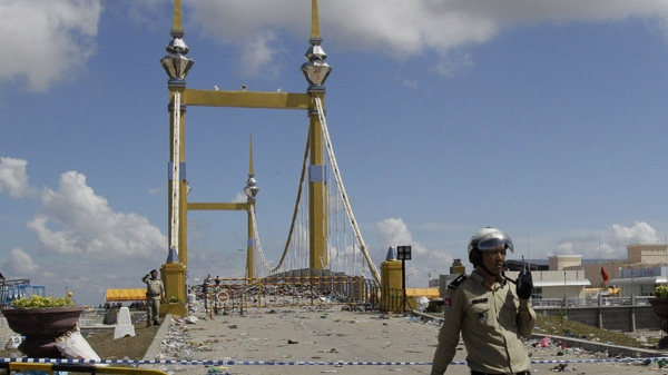 Cambodian police officers stand near the barricade set up at a bridge where people stampeded during a water festival in Phnom Penh, Cambodia, Tuesday, Nov. 23, 2010. (AP Photo/Sakchai Lalit)