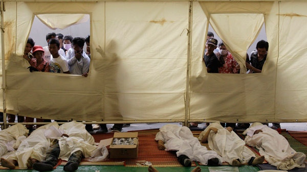 People look at the bodies of stampede victims through windows of a tent at Preah Kossamak Hospital in Phnom Penh, Cambodia, Tuesday, Nov. 23, 2010.  (AP / Sakchai Lalit)