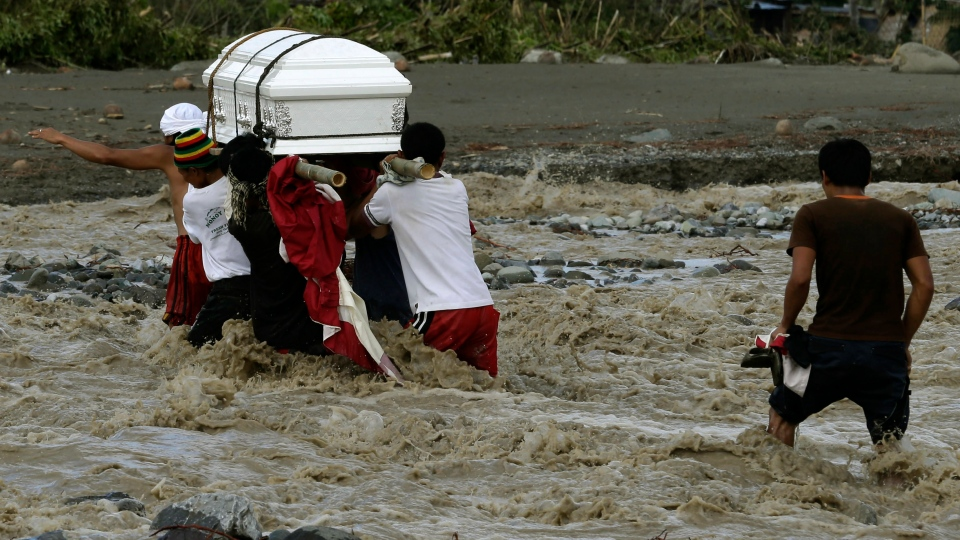 Relatives cross a river to bury their loved one, who died in a flash flood caused by Typhoon Bopha, in New Bataan township, Compostela Valley in the southern Philippines, Thursday, Dec. 6, 2012. (AP / Bullit Marquez)