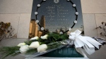 Fourteen white roses, in memory of the fourteen women students killed by a lone gunman, lie in front of the commemorative plaque at the University of Montreal on the 23rd anniversary of the Polytechnique massacre, Thursday, December 6, 2012, in Montreal. (Paul Chiasson / THE CANADIAN PRESS)