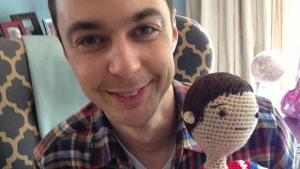 Jim Parsons, who plays Sheldon Cooper on The Big Bang Theory, holds up a crocheted version of himself. The crochet doll was sent to him from a Dawson Creek woman. SUPPLIED.