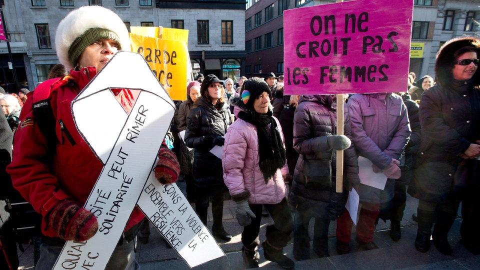 Women gather to protest against violence towards women in front of the Montreal courthouse on the 23rd anniversary of the Polytechnique massacre, where a lone gunman killed 14 women students at University of Montreal technical school, Thursday, Dec. 6, 2012. (Paul Chiasson / THE CANADIAN PRESS)