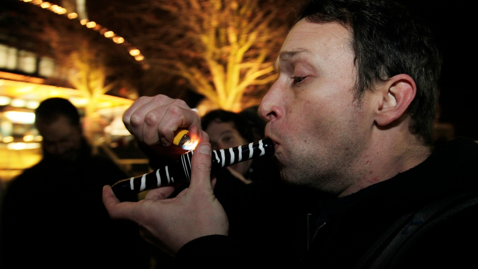 Gary Parrish smokes marijuana in a glass pipe just after midnight at the Space Needle in Seattle, Thursday, Dec. 6, 2012. (AP / Ted S. Warren)