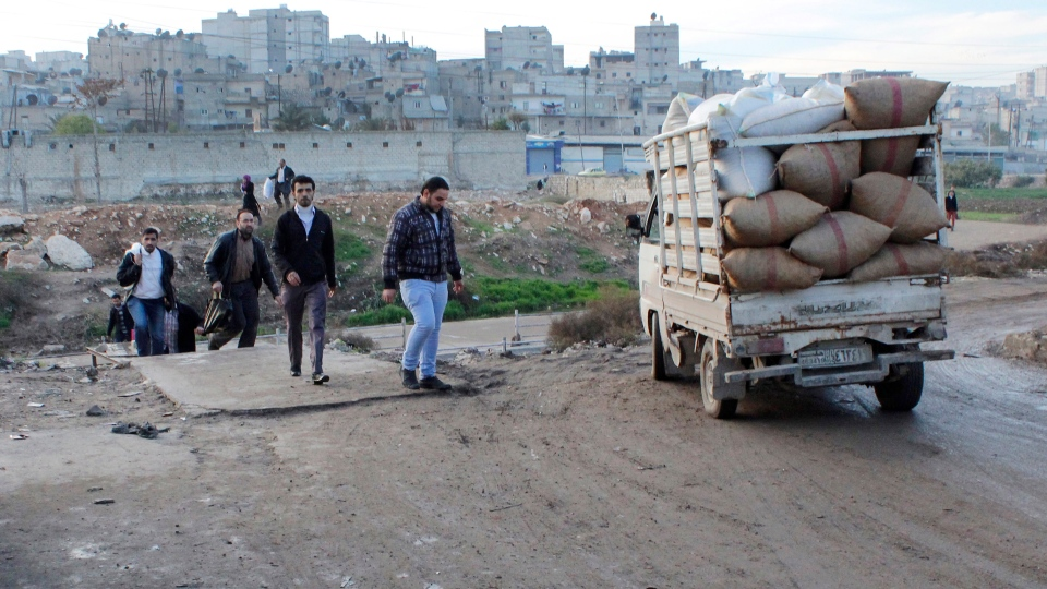 Syrian citizens cross from the area that controlled by the Syrian forces loyal to president Bashar Assad, to an area controlled by the Free Syrian Army, at the only crossing point between the two groups, in Aleppo, Syria, Wednesday Dec. 5, 2012. (AP / Abdullah al-Yassin)