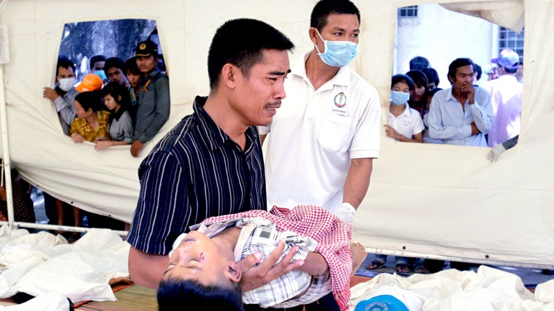 A Cambodian man carries the body of his son killed in a stampede, at Preah Kossamak Hospital in Phnom Penh, Cambodia, Tuesday, Nov. 23, 2010. (AP / Sakchai Lalit)