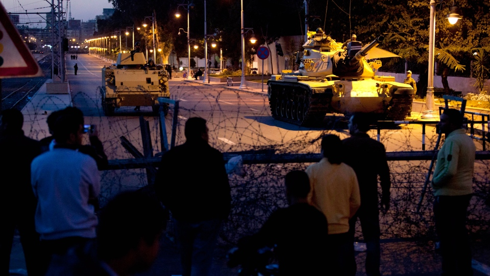 Egyptian army tanks are seen behind barbed wire securing the perimeter of the presidential palace during a protest by opponents of President Mohammed Morsi, in Cairo, Egypt, Thursday, Dec. 6, 2012. (AP / Nasser Nasser)