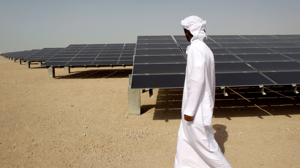 An Emirati man pass by 10mw photovoltaic plant at Masdar City in Abu Dhabi, United Arab Emirates, Sunday, Jan. 16, 2011. (AP / Kamran Jebreili)