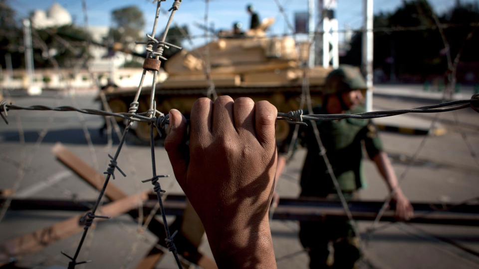 An Egyptian army tank is seen behind barbed wire securing the perimeter of the presidential palace while protesters on the other side chant anti President Mohammed Morsi slogans, in Cairo, Egypt, Thursday, Dec. 6, 2012. (AP / Nasser Nasser)