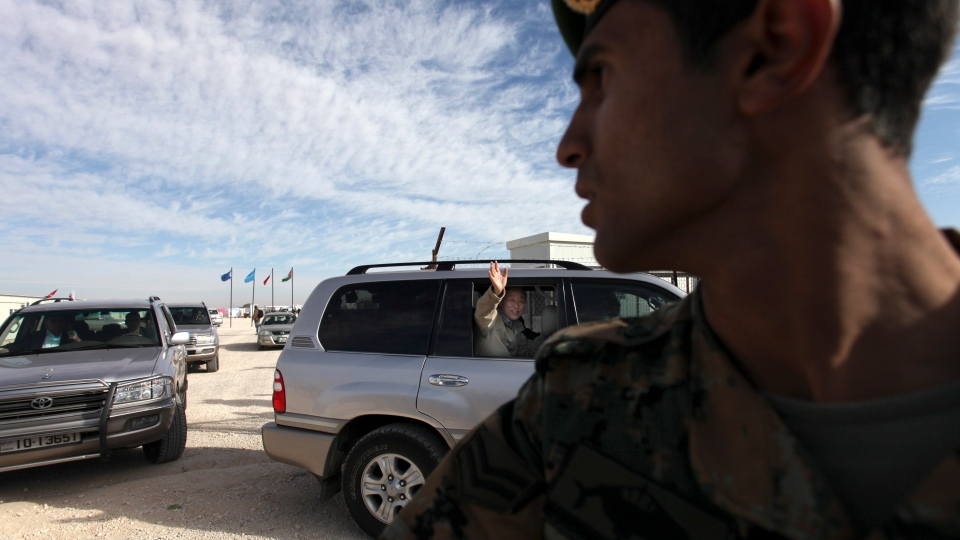The United Nations Secretary-General Ban Ki-moon waves to Syrian refugees from a vehicle as his convoy arrives at Zaatari refugee camp, in Mafraq, Jordan, near the Syrian border on Dec. 7, 2012. (AP / Mohammad Hannon)
