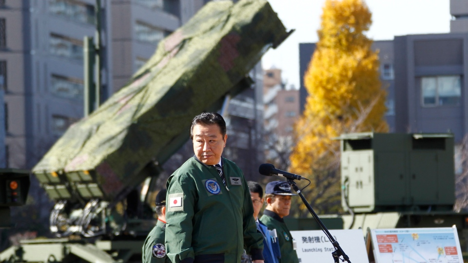 Japanese Prime Minister Yoshihiko Noda, standing by a ground-based Patriot Advanced Capability-3 interceptor, looks back as he speaks during his inspection tour to the Defense Ministry in Tokyo, Friday, Dec. 7, 2012. (AP / Koji Sasahara)