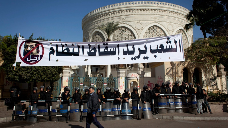 An Egyptian passes riot policemen guarding a gate of the presidential palace under a banner with a defaced picture of president Mohammed Morsi and Arabic that reads 'the people want to bring down the regime,' at the protests site, in Cairo, Egypt, Saturday, Dec. 8, 2012. (AP / Nasser Nasser)