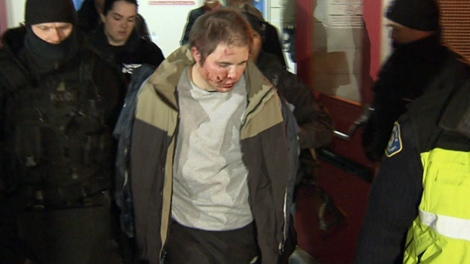 The man involved in the hostage crisis is taken to a waiting ambulance after receiving medical attention following the standoff at a community centre in Vancouver, early Wednesday, Nov. 24, 2010.
