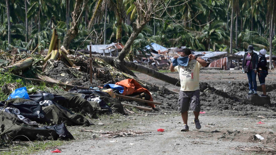 A resident covers his nose as he walks past typhoon Bopha's victims which are left unattended at New Bataan township, Compostela Valley in southern Philippines Saturday Dec. 8, 2012. (AP / Bullit Marquez)