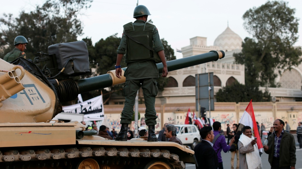 An Egyptian protester takes a picture with his mobile of another in front of an Egyptian army tank outside the presidential palace, background, in Cairo, Egypt on Saturday, Dec. 8, 2012.(AP / Hassan Ammar)