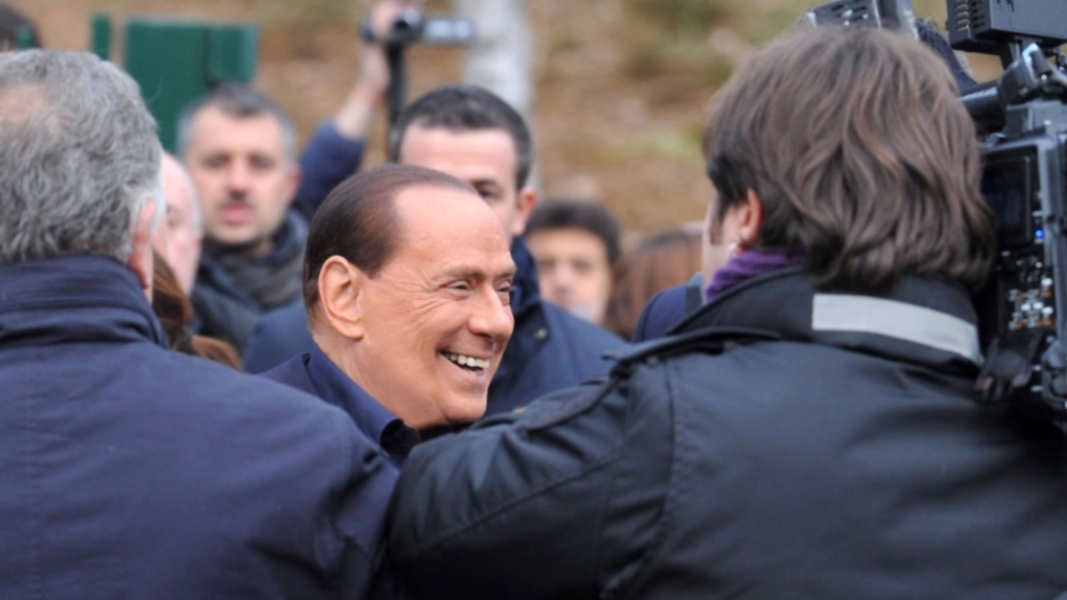 Billionaire media baron Silvio Berlusconi is surrounded by media as announces he is running for a fourth term as premier, during a visit to the AC Milan Milanello soccer training center, near Milan, Italy on Saturday, Dec. 8, 2012. (AP / Gianni Buzzi, AC Milan press office)