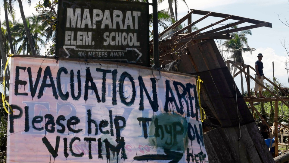 A typhoon victim rebuilds his damaged house near a sign asking for aid for victims of Typhoon Bopha at Maparat Township, Compostela Valley in southern Philippines Saturday Dec. 8, 2012. (AP / Bullit Marquez)