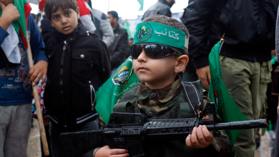 A Palestinian boy wears a green headband with the Arabic slogan 'Ezz Al-Din Al Qassam brigade' and green Islamic flags while holding a toy gun during a rally to commemorate the 25th anniversary of the Hamas militant group, in Gaza city, Saturday, Dec. 8, 2012. (AP / Adel Hana)