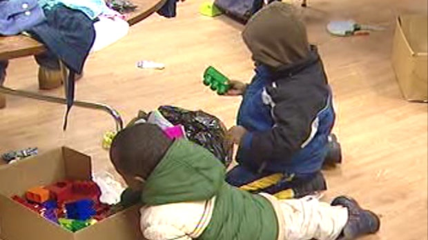 Two young children play with toys donated for newcomer families at the Toys and Clothing Party hosted by KidBridge Saturday.