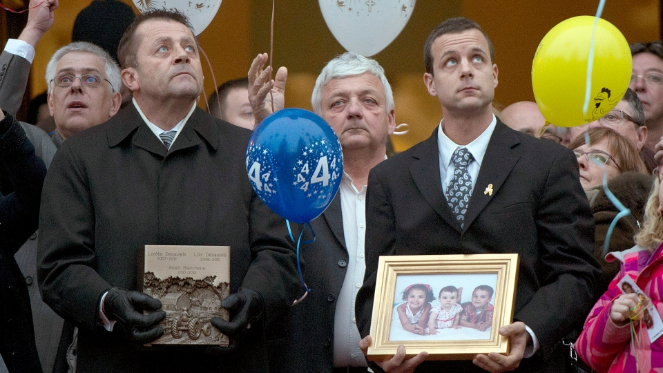 Patrick Desautels, right, father of Loreilie (5), Loic (4) and Anais (2), looks up as balloons are released following their funeral in Acton Vale, Que., Saturday, Dec. 8, 2012. (Graham Hughes / THE CANADIAN PRESS)