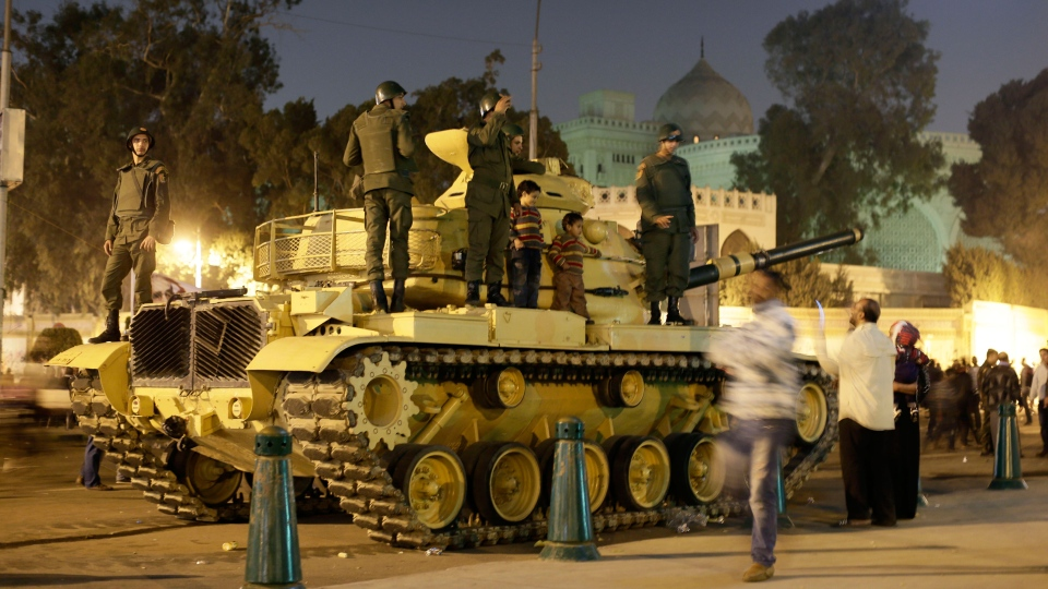 An Egyptian protester takes a picture with his mobile of his children on top of an Egyptian army tank outside the presidential palace, background, in Cairo, Egypt, Saturday, Dec. 8, 2012. (AP / Hassan Ammar)