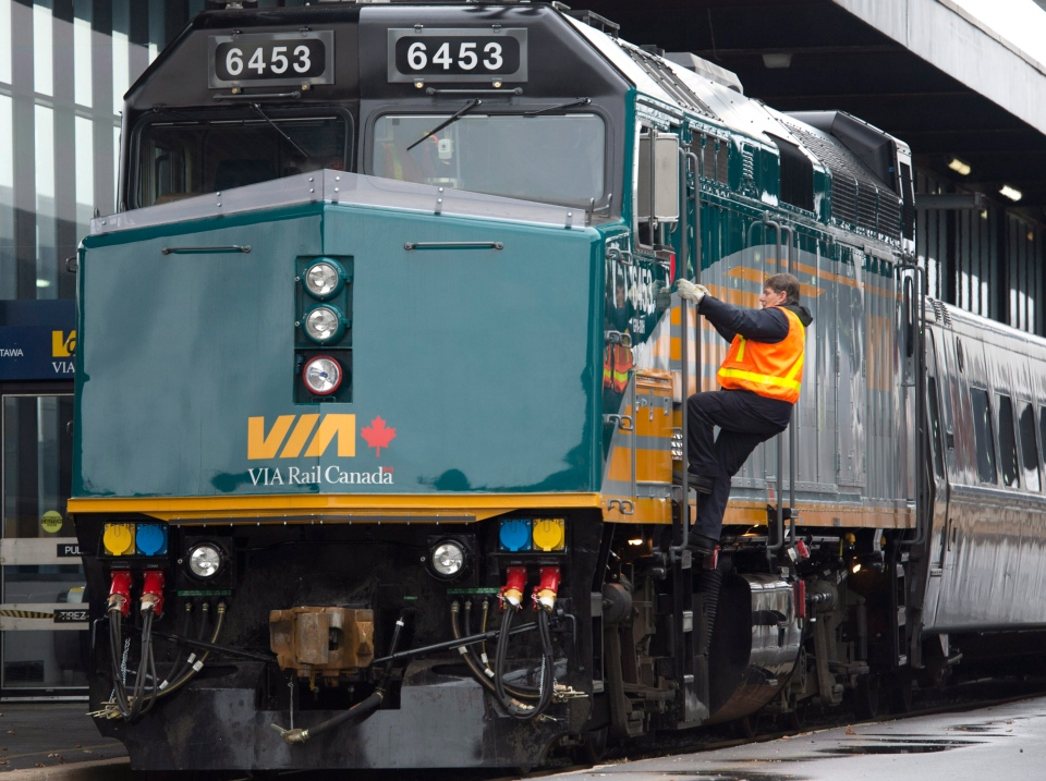 A Via Rail employee climbs aboard an F40 locomotive at the train station in Ottawa on Monday, December 3, 2012. (Adrian Wyld / THE CANADIAN PRESS)