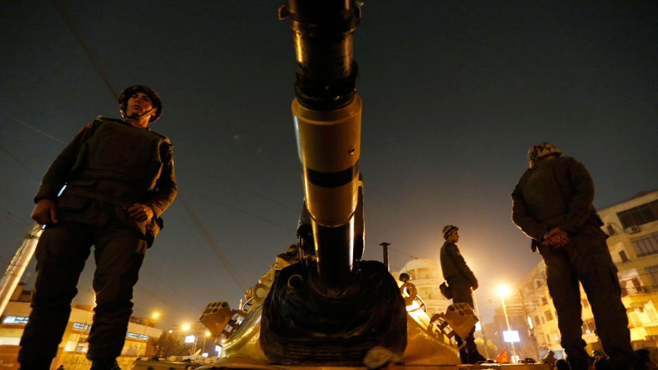 Soldiers stand guard on top a tank in front of the presidential palace in Cairo, Egypt, Sunday, Dec. 9, 2012. (AP / Petr David Josek)
