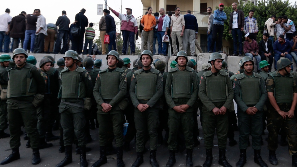 Egyptian army soldiers stand guard as protesters stand on top of cement blocks near the presidential palace in Cairo, Egypt, Sunday, Dec. 9, 2012. (AP / Hassan Ammar)