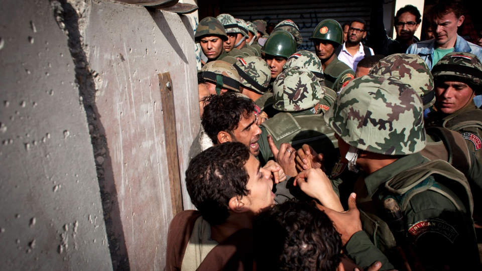 Egyptian protesters scuffle with army soldiers near the presidential palace in Cairo, Egypt, Sunday, Dec. 9, 2012. (AP / Nasser Nasser)