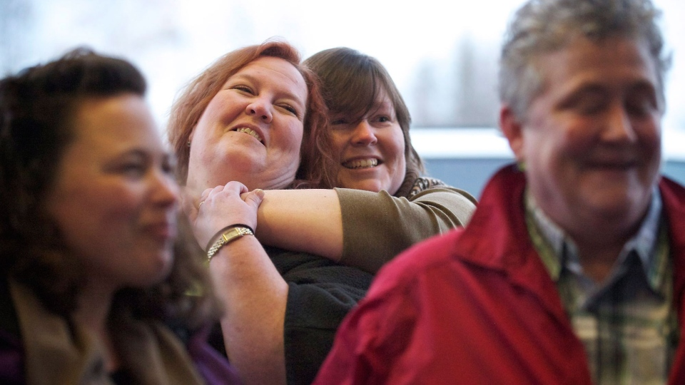 Samantha Petshow, center left, 43, and her partner Kim Hyder, 41, both of Vancouver, Wash. embrace as same-sex couples line up to apply for marriage licenses at Clark County Auditor's Office, in Vancouver, on Thursday Dec. 6, 2012. (AP / The Columbian, Zachary Kaufman)