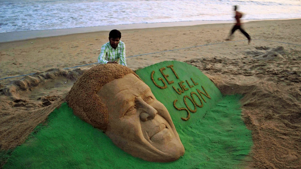 Artist Sudarshan Pattnaik gives finishing touches to a sand sculpture of former South African President Nelson Mendala with a message, at a beach in Puri, about 67 kilometers from the eastern Indian city of Bhubaneswar, India, Sunday, Dec. 9, 2012. (AP)