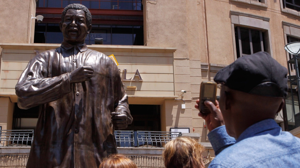 People take photos of the giant statue of former president Nelson Mandela, in Mandela Square, Johannesburg, South Africa, as they prayed for the former president's health Sunday Dec. 9, 2012. (AP / Denis Farrell)