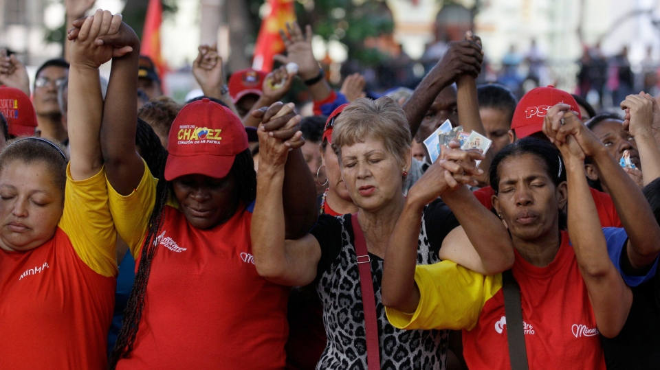 People pray during a demonstration in support of Venezuela's President Hugo Chavez at the Simon Bolivar square in Caracas, Venezuela, Sunday Dec. 9, 2012. (AP / Fernando Llano)