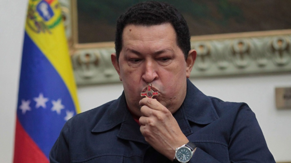 Venezuela's President Hugo Chavez kisses a crucifix during a televised speech form his office at Miraflores Presidential palace in Caracas, Venezuela, Saturday, Dec. 8, 2012. (Miraflores Press Office / Marcelo Garcia)