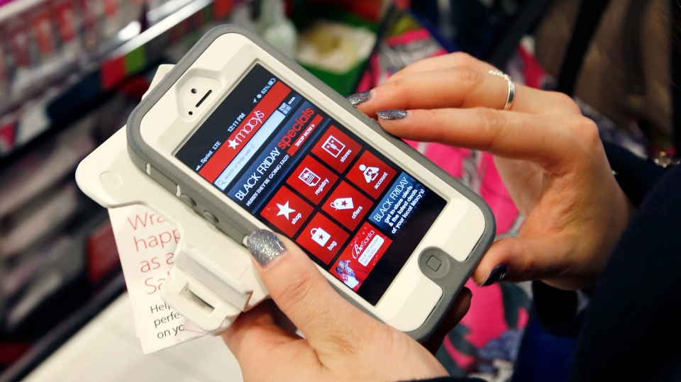 Tashalee Rodriguez, of Boston, uses a smart phone app while shopping at Macy's in downtown Boston, Friday, Nov. 23, 2012. (AP Photo/Michael Dwyer)
