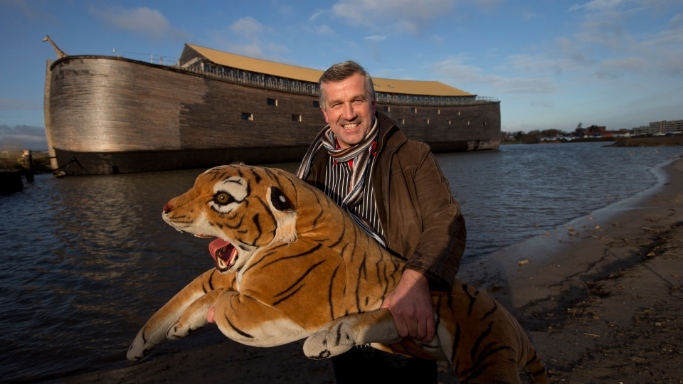 Johan Huibers poses with a stuffed tiger in front of the full scale replica of Noah's Ark after being asked by a photographer to go outside with the animal in Dordrecht, Netherlands, Monday Dec. 10, 2012. (AP / Peter Dejong)
