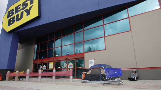 Nguyen Nguyen, 20, of Houston, sits next to his tent first in line outside of a Best Buy store in The Woodlands, Texas on Thursday, Nov. 25, 2010. (AP Photo / The Courier, Eric S. Swist)