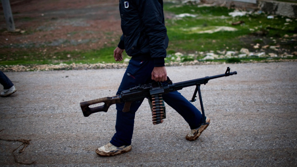 A Free Syrian Army fighter holds his weapon as he prepares himself for advance, close to a military base, near Azaz, Syria, Monday, Dec. 10, 2012. (AP / Manu Brabo)