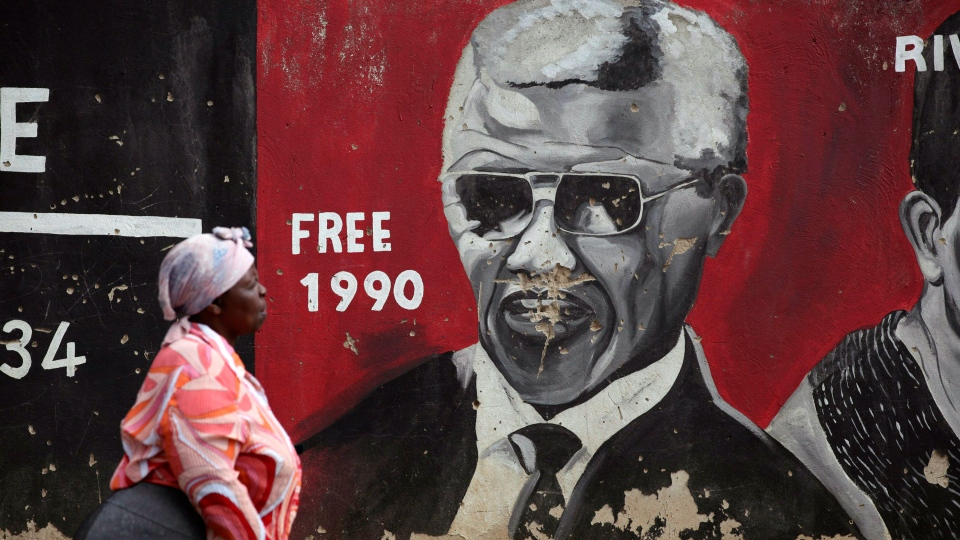 A woman walks past a mural showing former South African President Nelson Mandela in the Soweto area of Johannesburg, South Africa Sunday, Dec. 9, 2012. (AP / Jon Gambrell)