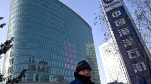 A man walks past the headquarters of the state-owned China National Offshore Oil Corp. (CNOOC) in Beijing, China Saturday, Dec. 8, 2012. (AP / Andy Wong)