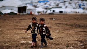 Syrian boys, whose family fled their home in Idlib, walk to their tent, at a camp for displaced Syrians, in the village of Atmeh, Syria, Monday, Dec. 10, 2012. (AP / Muhammed Muheisen)