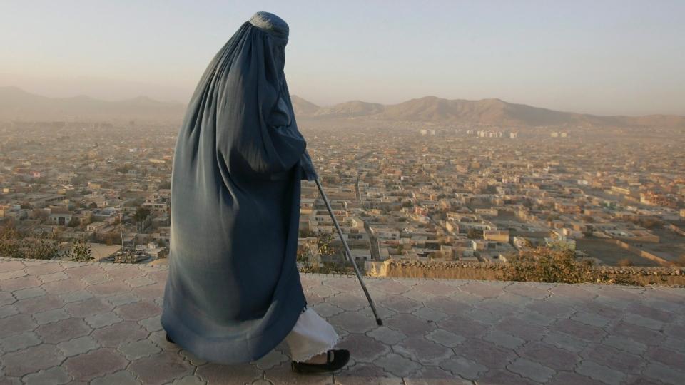 Zakera, a burqa-clad Afghan woman, walks for exercise on a hill overlooking Kabul, Afghanistan. (AP Photo/Ahmad Nazar)
